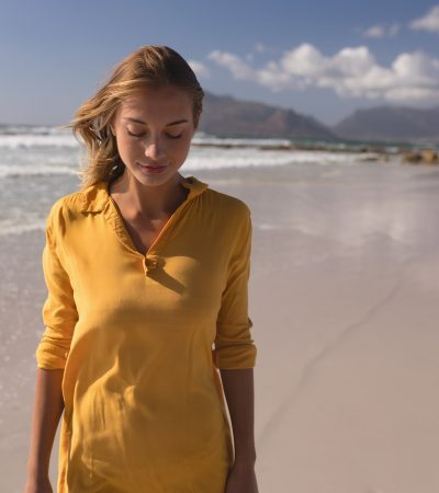 Beautiful young woman standing with eyes closed on the beach