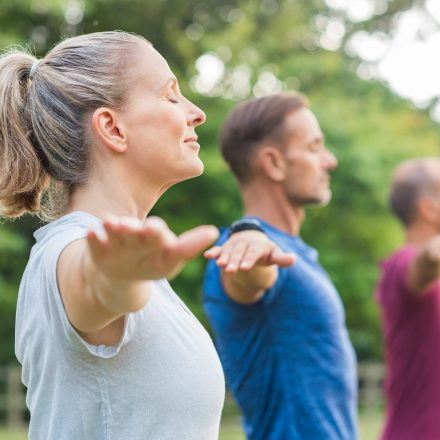 Group of senior people with closed eyes stretching arms at park. Happy mature people doing yoga exercise outdoor on a bright morning. Yoga class with woman and men doing breath exercising with stretched arms.